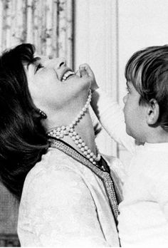 John Kennedy Jr. plays with his mother's pearl necklace at The White House, 1962
