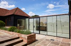 Frameless structurally glazed walkway link between converted barn houses with slimline metal framed doors House Extension Design, Glass Extension, House Design, Rural House, House In The Woods, Glass Walkway, Converted Barn, Glass Room, Corner House
