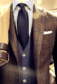 Plaid tweed jacket paired with cashmere cardigan, striped shirt, solid navy necktie, white pocket square.