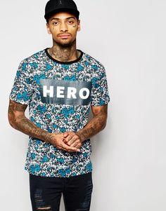 """T-shirt imprimé par Hero's Heroine Jersey de coton Ras du cou Logo imprimé sur la poitrine Coupe classique taillant normalement Lavage en machine 100% coton Le mannequin porte l'article en taille Medium et mesure 185,5 cm (6'1"""")"""