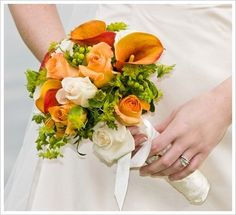 Mango calla lilies with white and orange roses with green berries in this hand tied bouquet.