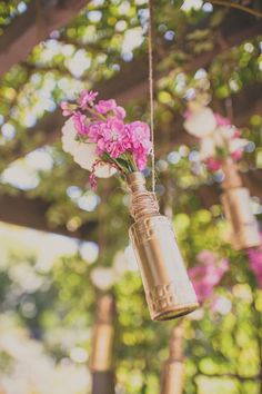 Wedding reception decor: fuchsia flowers hung in gold painted jars