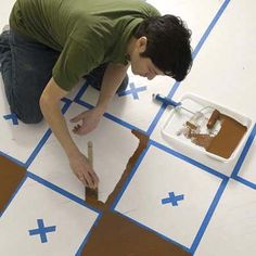 starting to paint the dark squares in a checkerboard pattern on a wood floor