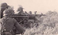 A German MG34 machine gun crew. Note the elevated binoculars behind the gun, scanning the horizon.