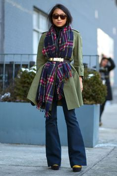 Keeping warm while taking in the sights is a cinch: Try a skirted overcoat, classic plaid scarf, and flared jeans pulled together (literally) with a chic belt.