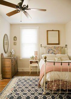 chambre avec ventilateur et un lit en fer