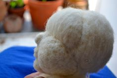 forming a doll's head with stitch and needle felting