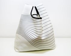 Reusable Shopping Bag, folded into a triangle, blue and white cotton, edged in black ribbon..