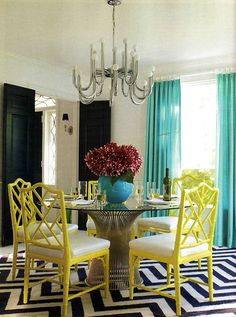 Love the black and white chevron stripe rug with yellow bamboo chairs!! Also really feeling painted drapery hardware , loves a good faux finish.