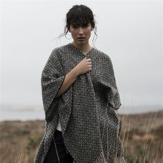 This luxury charcoal grey Donegal Tweed Eske cape with a subtle contrasting blue, purple and red check is woven and made in our mill in Donegal, Ireland. A great all-year-round piece. Style with the Cream Darcy Silk Blouse and Fahan Black Tailored Fit Trousers.