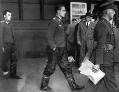 """German bomber crew emerges from a London Underground station after bailing out over the English countryside and taken prisoner. Both Germans are unrestrained and the English MP carries the paperwork in hand as he is about to surrender his prisoners to Army authorities. An older man and a porter in the background look on."" via waralbum.ru"