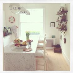 Ella Woodward's kitchen - LOVE the marble bar, light shades and shelves. And crate. And whiteness.