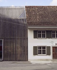 marazzi reinhardt slots farmhouse intervention between traditional swiss buildings
