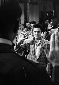 Still in the plaid sport coat, Elvis is sworn into the U. S. Army by Maj. Elbert Turner.