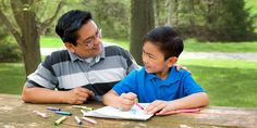 As a little boy draws a picture, his father puts his arm around him