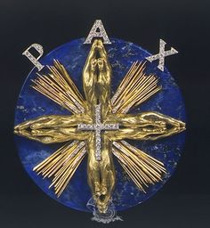Dalí i Domènech, Salvador Peace Medal  Date 1954 Dimensions 8.40 x 7.70 x 1.80 cm Ubication Dalí · Jewels Technique:  Yellow Gold 18 Kt (750 mils); 13-14 Kt yellow gold (541-583 milliseconds) ,; Diamonds (97), brilliant cut (round) and 8/8; Lapis lazuli, round plate, polished