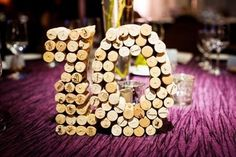 To highlight the amazing vineyard wedding decor of your venue, you can make cool wine-themed table numbers. The most popular idea here is using wine corks to hold the cards with table numbers. You can also attach several corks to create a table number.