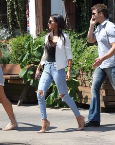 Selena Gomez street style. Wearing high waisted ripped light jeans with black tank top white blazer and nude pumps