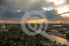 A wide angle view of rainy sunset clouds above river and a large city of Moscow.