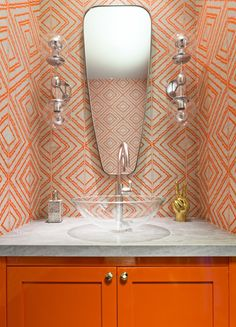 """""""We had fun in small spaces such as the powder room, where we selected a vibrantly patterned wallpaper and painted the vanity in Farrow & Ball's Charlotte's Locks,"""" says Quin. A pair of sconces from the Future Perfect and a Kelly Wearstler mirror temper the room's more vibrant elements."""