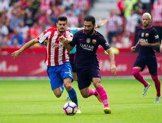Arda Turan of FC Barcelona duels for the ball with Sergio Alvarez of Real Sporting de Gijon during the La Liga match between Real Sporting de Gijon...