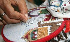 An artisan embroiders a Baiton Kantha