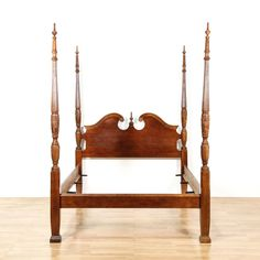 This Chippendale four poster bed is featured in a solid wood with a glossy mahogany finish. This queen sized bed frame has a curved broken pediment top and tall carved spindle posts with fluting. Stunning bed perfect for a regal bedroom! #americantraditional #beds #bedframe #sandiegovintage #vintagefurniture