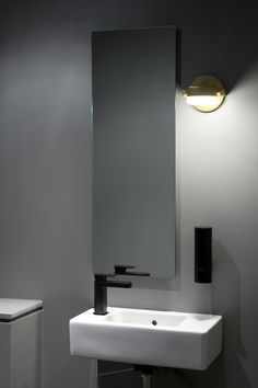 Rich Brilliant Willing Monocle Sconces with wall mounted fixtures in the bathrooms at Falken Reynolds Sai Woo