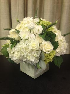 White floral centerpiece with lots of hydrangea.