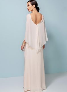 Close-fitting lined dress has side pleating and attached cape.
