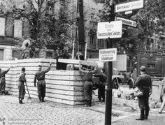 "Replacement of the Stone Wall with a Concrete Wall (July 1, 1963)-Starting in 1963, portions of the original stone Wall were replaced with concrete. This photo shows work being done at Bernauer Straße. The two signs on the right are still within the Western sector – but just barely. One warns: ""End of the French sector""; the other issues the following condemnation: ""Roadblock caused by the Wall of Shame."""