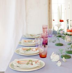 Dinner party set up with a light purple tablecloth, colorful glass cups, decorative candlesticks and decorations, and brass cutlery
