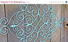 Large wrought iron wall hanging refinished in a beautiful aqua finish, distressed and sealed. Fleur de lis design and loads of swirls! Beautiful