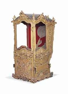 AN ITALIAN GILTWOOD AND POLYCHROME-PAINTED SEDAN CHAIR, ROME, 18TH CENTURY. The domed leather roof above a scrolling foliate-carved frame, the panels carved with arabesques, grotesque masks and beasts, above glazed panels painted with putti, floral swags and caryatids, the interior with red velvet lining centred by a needlework panel depicting a unicorn and monstrance. Provenance: By repute, Noble family Lanza di Trabia, Sicily.