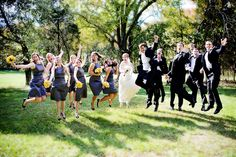 the classic wedding party jumping in the air pose - bridesmaids are wearing purple dresses with yellow bouquets, bride is wearing white dress, and groomsmen are wearing black and white suits - photo by North Carolina based wedding photographers Cunningham Photo Artists