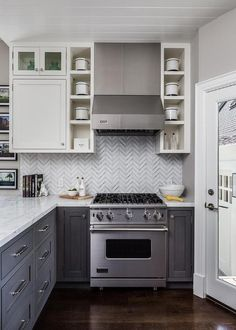 White and gray kitchen features white upper cabinets and distressed gray lower cabinets paired with white marble countertops and a gray herringbone tile backsplash. A small Viking hood, flanked by open shelving, stands over a small Viking range next to a corner glass door which leads to the backyard.