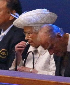 Queen Elizabeth II puts on her lip stick as she attends the Opening Ceremony for the Glasgow 2014 Commonwealth Games at Celtic Park while Prince Philip, Duke of Edinburgh resting his eyes.