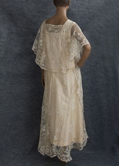 Princess lace wedding dress, c.1923. Made from ivory cotton tulle hand appliquéd with bouquets of princess lace flowers, the loose, unconstructed style slips on without closures. It is comfortable and effortless to wear. Near the neckline and on the sleeves, the charming appliquéd flowers cluster closely together, as if to compete with one another to adorn the beauty of the wearer.