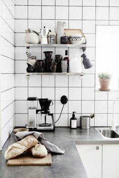 White square tiles with darker grey grout. Mixing a traditional size and shape of tile with a more contemporary looking grout finish