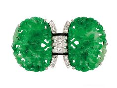 An Art Deco Jadeite, Diamond and Platinum Brooch, Ellis Bros., circa 1925  The twin jadeite plaques carved as a pair of butterflies amongst flowers, centering a diamond-set arch accented by black enamel, mounted in platinum and 18k white gold, signed Ellis Bros., French assay marks