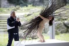 """A visitor takes a picture of """"Woman with sticks"""" by artist Ron Mueck, at the Fondation Cartier pour l'art contemporain, on April 15, 2013 in..."""