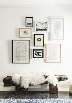 Eclectic art wall of modern artwork over a rustic wood bench - Gallery Wall Ideas & Decor