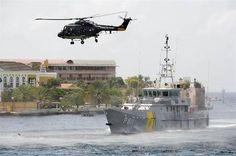 Helikopter en schip van de kustwacht in actie.