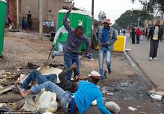 Sick: As Emmanuel Sithole lay injured in the gutter another thug saw what was going on and joined in the attack using a knife to stab him repeatedly while the first attacked continued to beat him with the wrench