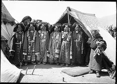 Photographer:  Rabden Lepcha?,  Collection:  Sir Charles Bell,  Date of Photo:  March 1st 1921,  Region: Lhasa, Lubu. Four Maids of Honour and two assistants who will serve chang or barley beer to the Yaso officials at the ceremony of the Preparation of the Camp at Lubu, standing outside decorated tents. The women wear coral headdresses, turquoise inlaid amulet boxes or gau at the neck and waist, Lhasa style turquoise ear ornaments, and strings of pearls, corals and other precious stones.