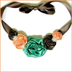 Elegant DIY twisted satin rose necklace!  Beth uses some of our pre-made loose satin roses paired with a simple satin ribbon and a couple of sparkling rhinestone embellishments to quickly put together a gorgeous one-of-a-kind necklace! Join her on the blog as shows how to make your own!