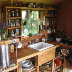 A tiny home kitchen with storage all around the window.