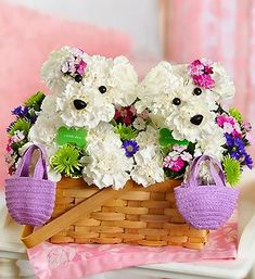 """Furever Friends™️   Two's company with our delightful, double-sized a-DOG-able®️️ bouquet. Ideal for surprising your best friend, sister, Mom or any close friend, this playful pair of puppy-shaped white carnation arrangements is surrounded by a gathering of colorful fresh blooms. With matching pink floral accents and mini purple totes, these """"friends furever"""" are ready to celebrate anything from a birthday bash to a bridal shower to a day at the spa."""