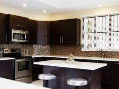 Dark cabinets and bright white countertops create the ultimate contrast in this streamlined kitchen. Tones of bronze and gold in the mosaic tile backsplash give the kitchen an appealing gleam.