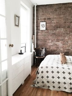 Sunny bedroom with IKEA Besta, Pia Wallen, exposed brick wall, and two cats in NYC apartment // owned by graphic designer behind children's brand www.OMAMImini.com